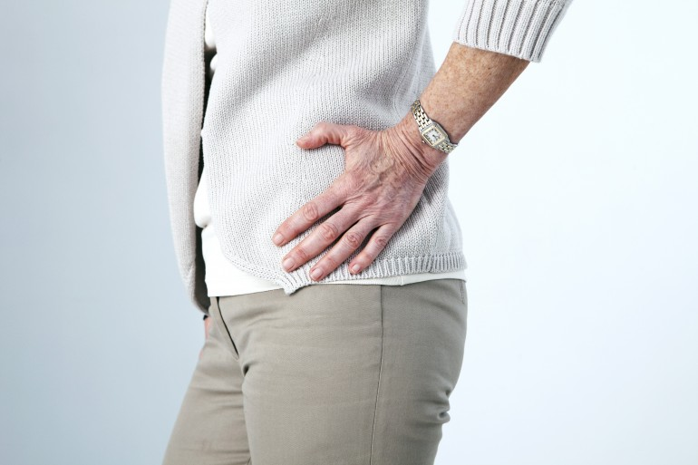 Elderly womain holding hip in pain